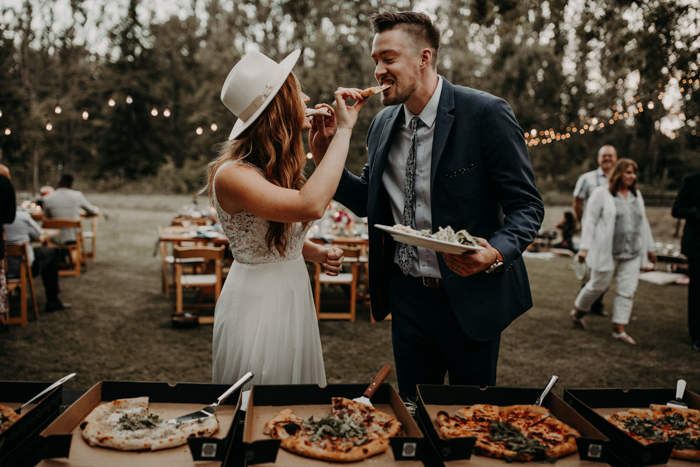 bride and groom feeding each other pizza