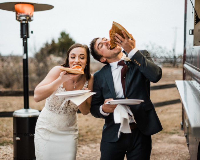 Pinterest worthy of photo of a bride and Groom enjoying slices of pizza